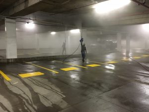 pressure washing overhead pipes in a parking garage
