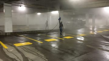 Power washing overhead pipes in a parking garage - parking garage pressure washing in Dallas and Fort Worth. C & D Commercial Services will clean your property.